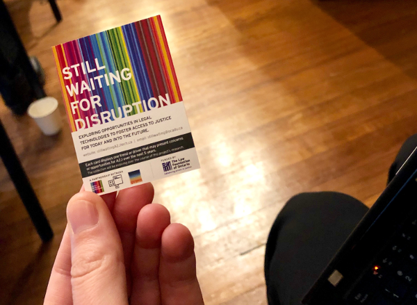Person holding a small postcard that says Still Waiting for Disruption