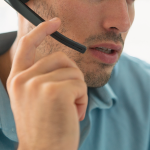 Extreme close up of a man talking into a phone headset