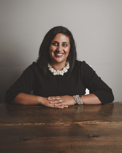 Neha Chugh, wearing a black dress and pearl necklace