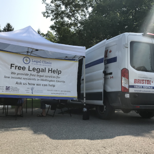 A white ban parked beside a white tent and banner that says Free Legal Help