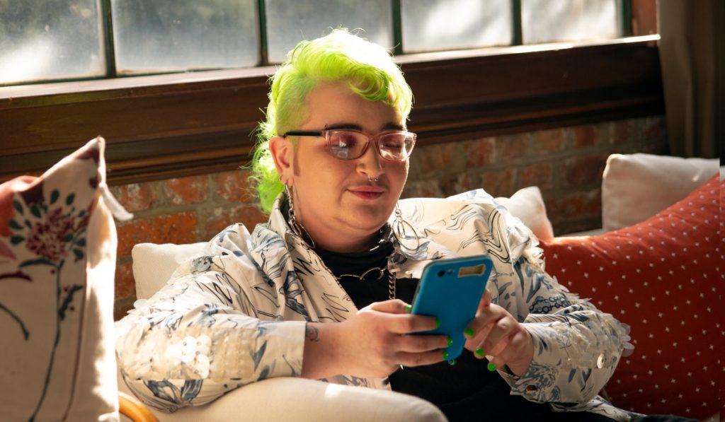 Une jeune personne aux cheveux teints en vert, assise sur un canapé et regardant leur téléphone