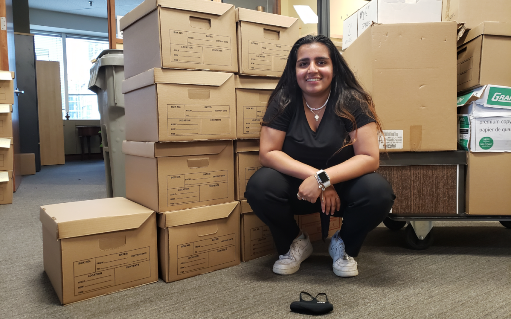 Young woman with long dark hair sitting in front of many moving boxes in a business office